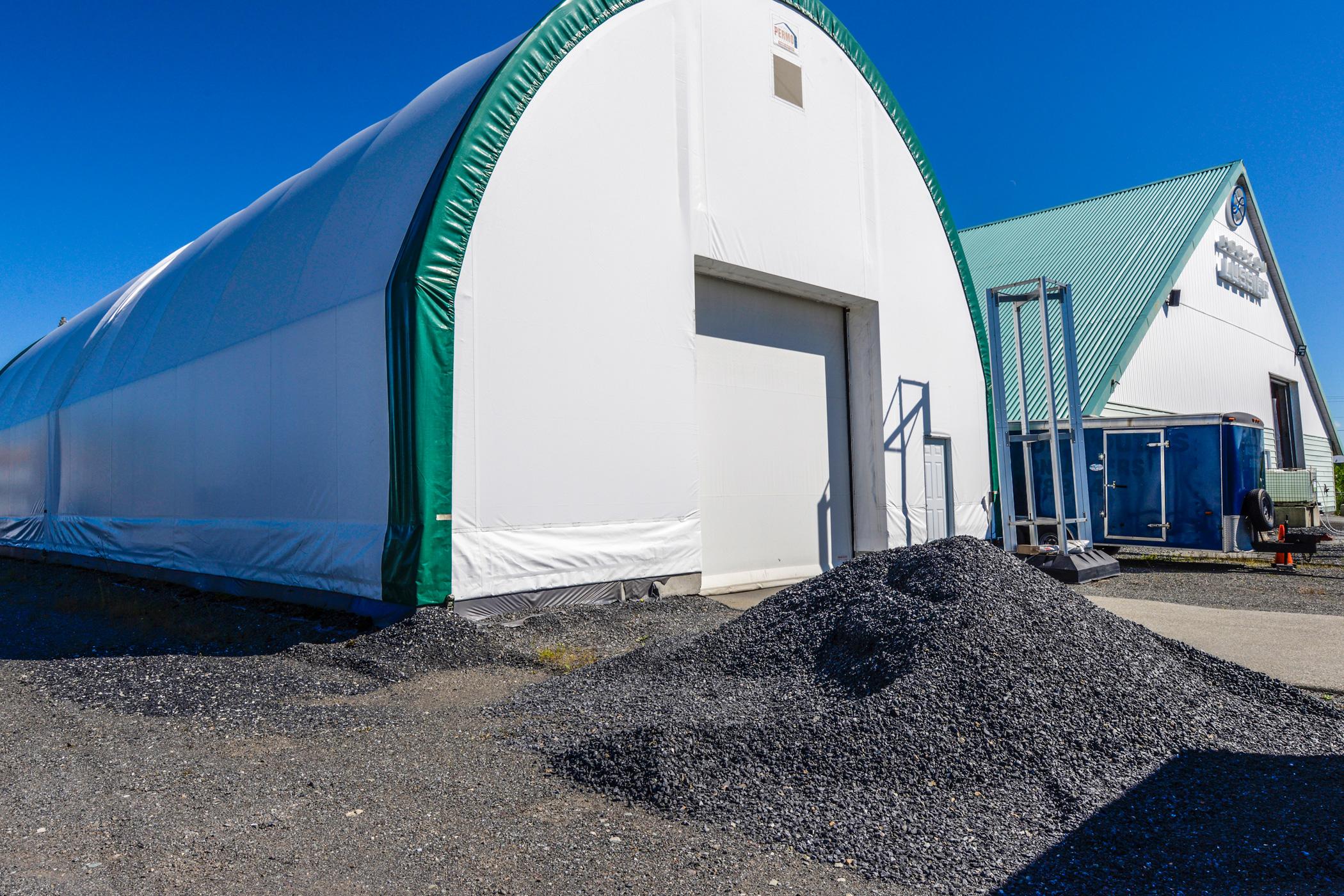 Permodome vert avec porte de garage et sable noir
