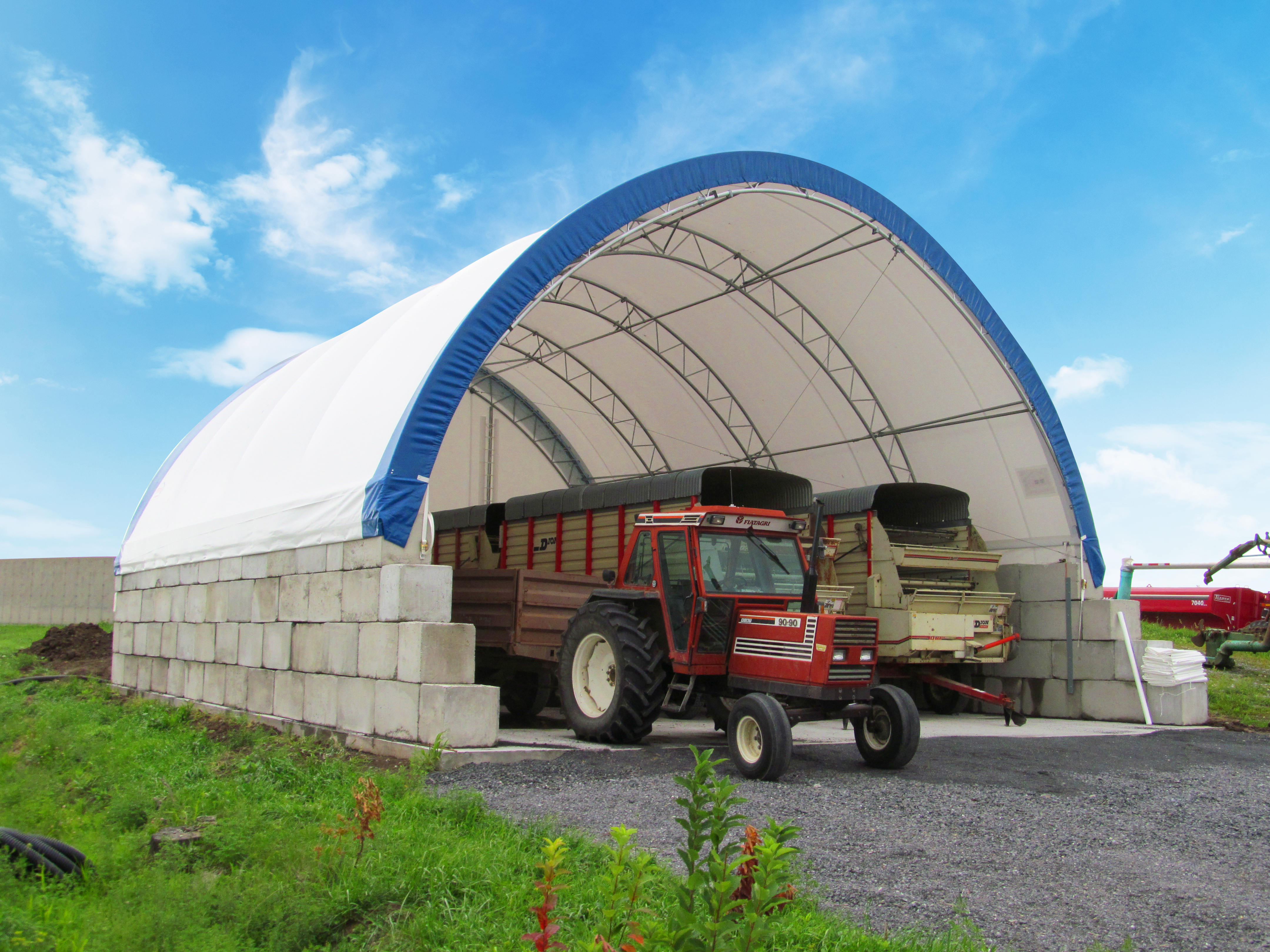 Permodome bleu avec un tracteur rouge et des wagons